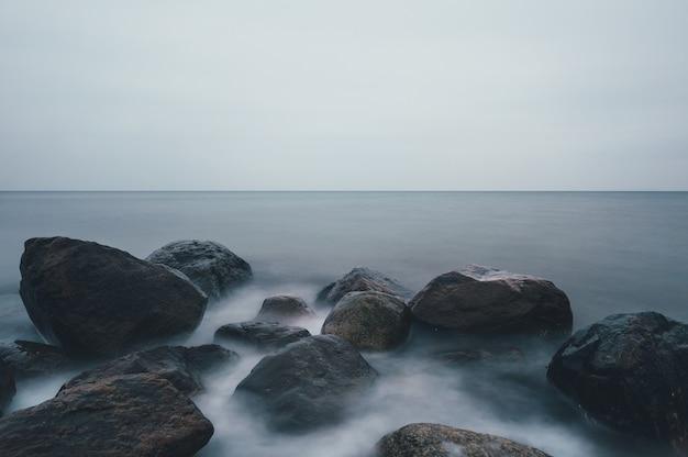 Hipnotyzujące ujęcie skalistego wybrzeża pod zachmurzonym niebem w ostsee w niemczech
