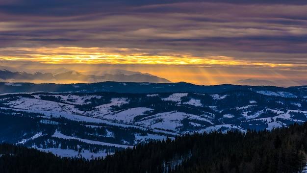 Hipnotyzujące widoki ośnieżonych łańcuchów górskich na tle zachodu słońca i pochmurnego nieba. miejsce na reklamę. koncepcja zimowej rekreacji górskiej