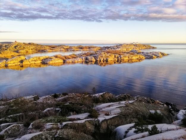 Hipnotyzujący jasny wschód słońca nad plażą w stavern w norwegii