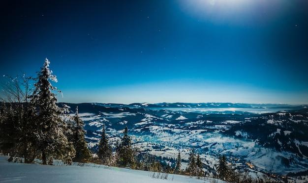 Hipnotyzujący krajobraz ośnieżonego stoku narciarskiego na tle świerkowego lasu i pasm górskich w świetle księżyca i błękitnego nieba w pogodny, mroźny zimowy wieczór. koncepcja rekreacji na świeżym powietrzu zimą