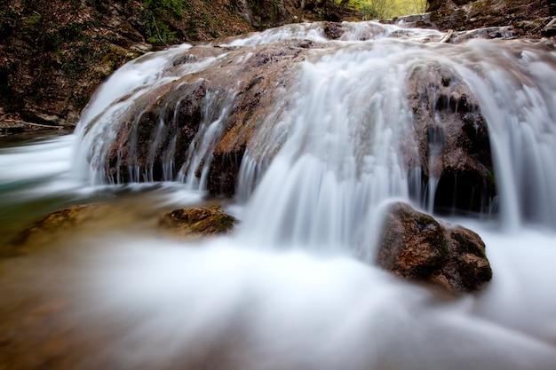 Hipnotyzujący malowniczy wodospad z górskiej rzeki i zalewający kamienie.