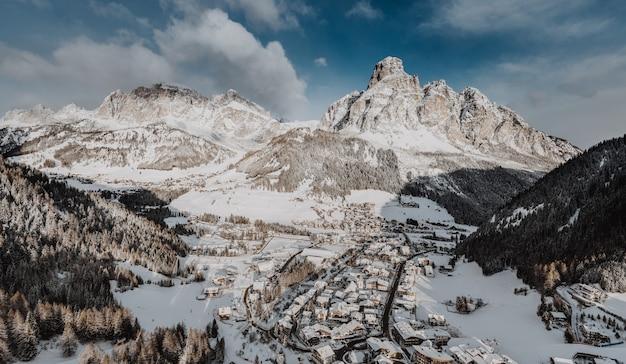 Hipnotyzujący widok małego miasteczka w zimie otoczonego górami skalistymi pokrytymi śniegiem