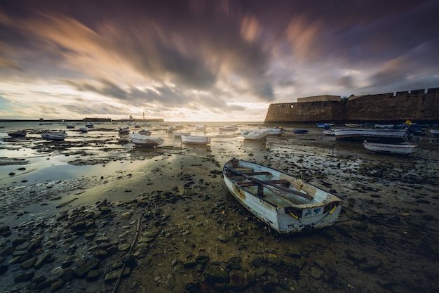 Hipnotyzujący widok na morze z zaparkowanymi małymi łodziami pod malowniczym zachmurzonym niebem
