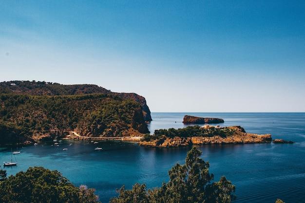 Hipnotyzujący widok na skały na brzegu morza pod błękitnym niebem