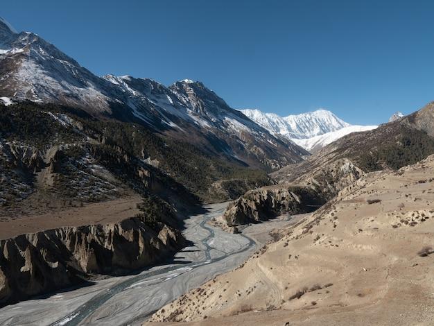 Hipnotyzujący widok na strumienie wody przez góry pokryte śniegiem w nepalu