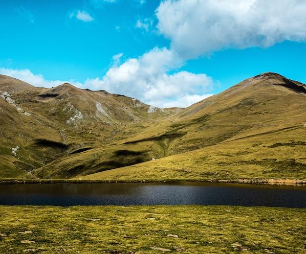 Hipnotyzujący widok na three peaks hill i jezioro pod zachmurzonym niebem w argentynie