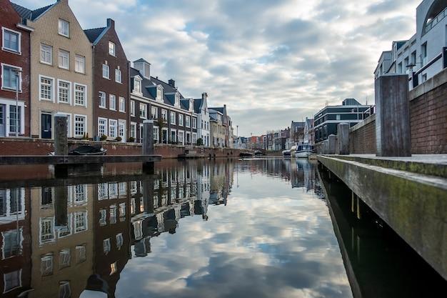 Hipnotyzujący widok odbicia budynków w rzece w pochmurny dzień