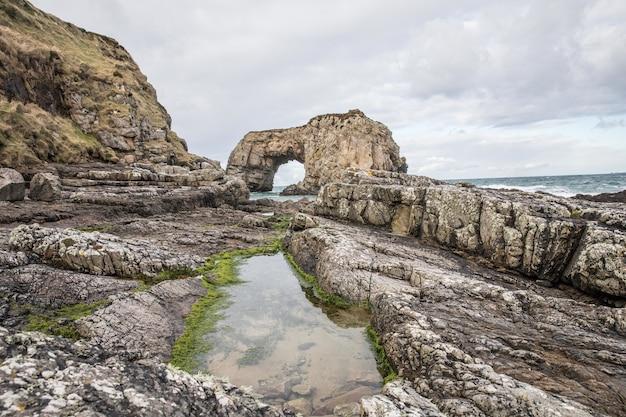 Hipnotyzujący widok skał na brzegu oceanu w pochmurny dzień