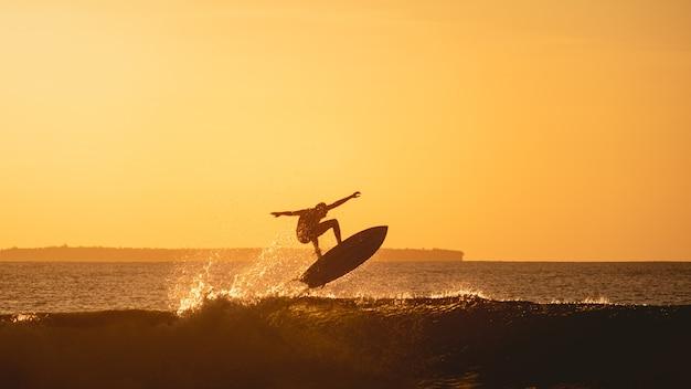 Hipnotyzujący widok sylwetki surfera na oceanie podczas zachodu słońca w indonezji