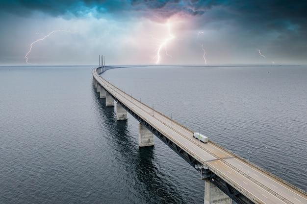 Hipnotyzujący widok z lotu ptaka mostu między danią a szwecją pod niebem z piorunami