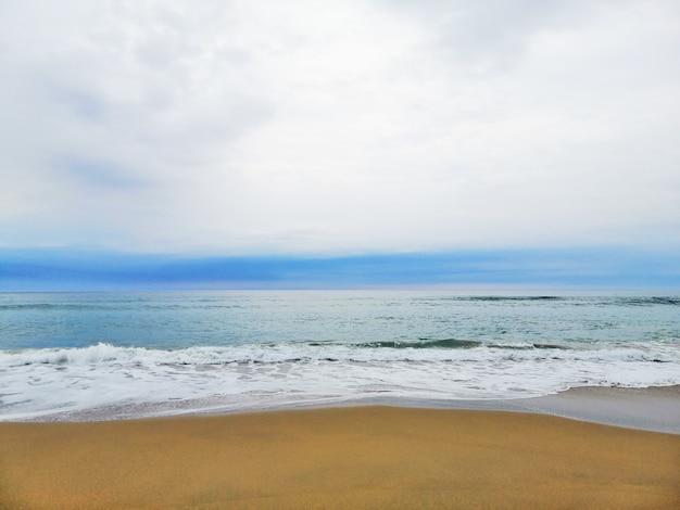 Hipnotyzujący wschód słońca nad piaszczystą plażą w kurorcie san sebastian w hiszpanii