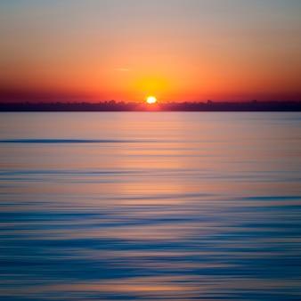 Hipnotyzujący zachód słońca nad czystym, błękitnym oceanem