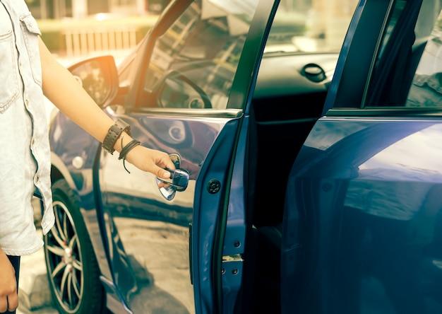 Hipster azjatycka dziewczyna otwiera niebieskie drzwi samochodu, efekt retro
