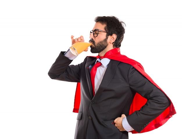 Hipster biznesmen ubrany jak superhero pije sok pomarańczowy
