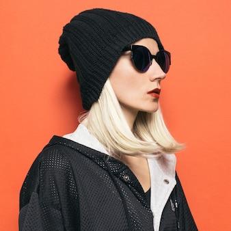 Hipster blond dziewczyna moda czapka. glamorous okulary przeciwsłoneczne. jesień zima sezon czarny styl
