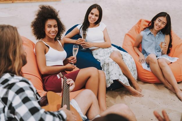 Hipster człowiek gra na gitarze na plaży uśmiechnięte dziewczyny