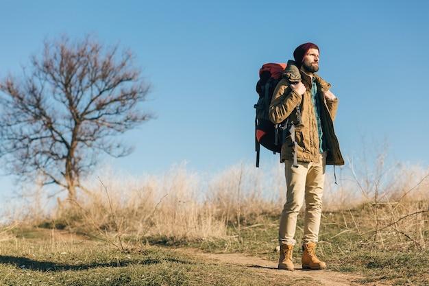 Hipster człowiek podróżujący z plecakiem w jesiennym lesie w ciepłej kurtce, kapeluszu, aktywny turysta, odkrywanie przyrody w zimnych porach roku