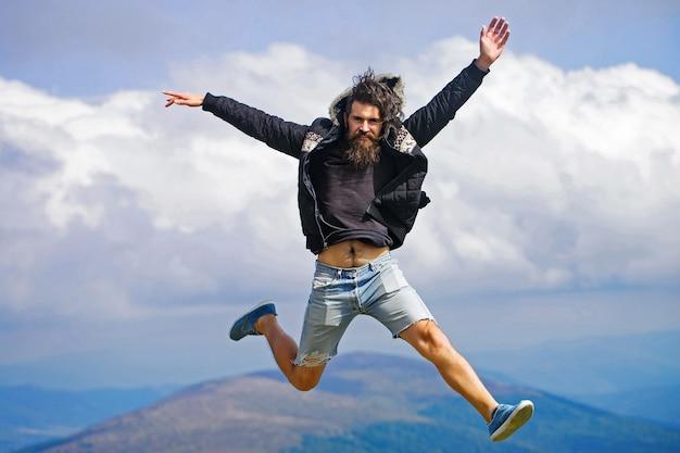 Hipster człowiek skacze na szczyt góry na pochmurnym niebie