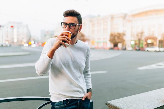 Hipster człowiek stojący z kawa na wynos