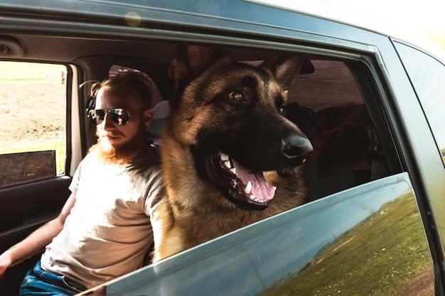Hipster człowiek w okularach i pies siedzi w samochodzie odkryty styl życia podróży przyjaźń koncepcja natura na tle