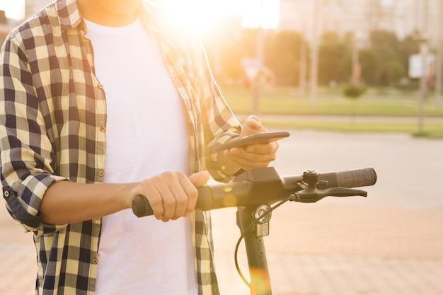 Hipster człowiek wynajmuje skuter elektryczny za pomocą aplikacji na telefon komórkowy z bliska kaukaski mężczyzna wynajmuje transport