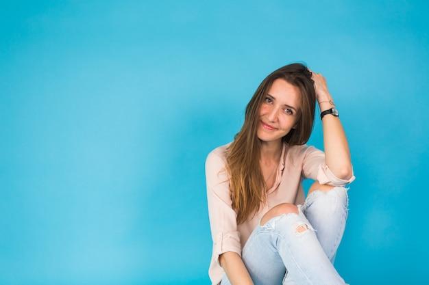 Hipster dziewczyna siedzi na podłodze przed niebieskim