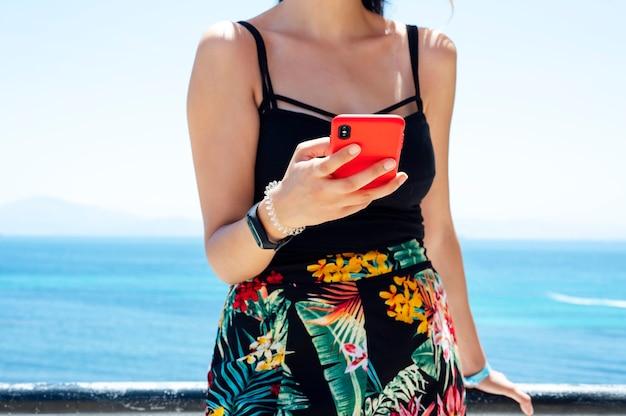 Hipster dziewczyna trzymać na inteligentny telefon gadżet na piaszczystej plaży, podróżnik czeka i używa telefonu komórkowego w kobiecej dłoni na tle seascape horyzont. turystyczny wygląd w niebieskim słońcu.