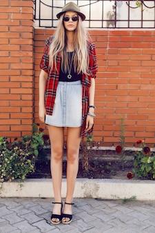 Hipster dziewczyna w retro kapelusz i okulary przeciwsłoneczne, pozowanie w pobliżu ściany grunge. mają długie blond, proste włosy i czerwoną koszulę.