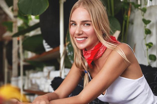 Hipster dziewczyna z chustką na szyi pozuje w kawiarni