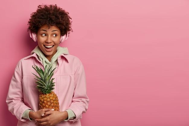 Hipster dziewczyna z radosną miną, szerokim uśmiechem, na duchu, lubi wolny czas, słucha ulubionego utworu przez słuchawki stereo, pozuje z egzotycznym ananasem, nosi bluzę z kapturem, patrzy na bok