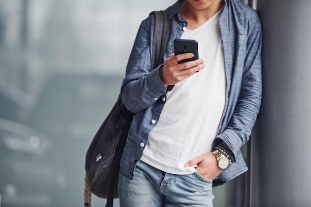 Hipster facet w ładne ubrania stoi w pomieszczeniu z telefonem w ręku