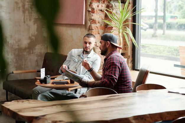 Hipster fotograf w czapce z daszkiem siedzi przy stole w kawiarni i omawia plan sesji zdjęciowej z asystentem po kwarantannie koronawirusa