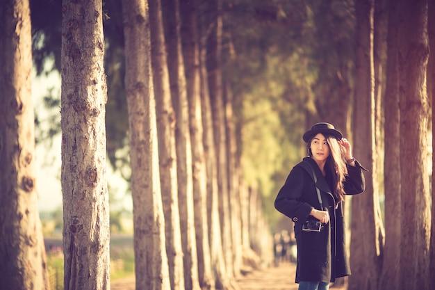 Hipster kobieta biorąc zdjęcie z aparatu fotograficznego na tle sosny
