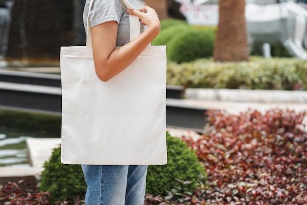 Hipster kobieta z białą bawełnianą torbę w parku