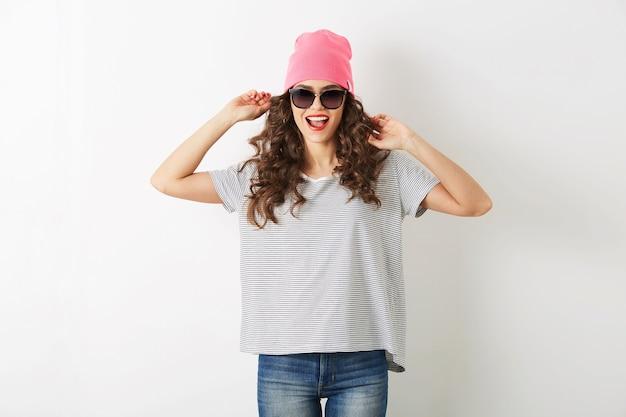Hipster ładna kobieta w różowym kapeluszu, okulary przeciwsłoneczne, taniec szczęśliwy, uśmiechnięta twarz, długie włosy, pozytywny nastrój, emocjonalny, strój w stylu hipster, letni trend w modzie, dżinsy i t-shirt w paski, na białym tle