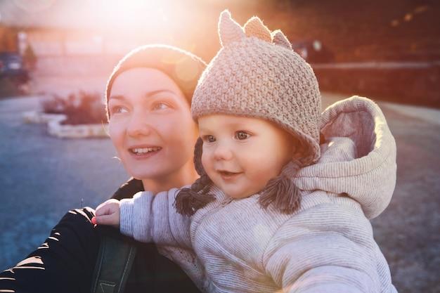 Hipster matka z dzieckiem ubrana w ciepłe ubrania, chodzenie w słoneczny dzień na świeżym powietrzu