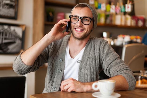 Hipster mężczyzna rozmawia przez telefon komórkowy w kawiarni