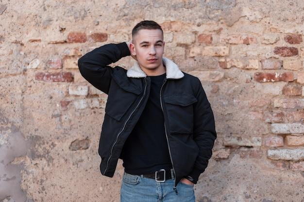 Hipster mężczyzna w modne ubrania z kurtką w pobliżu ściany z cegły