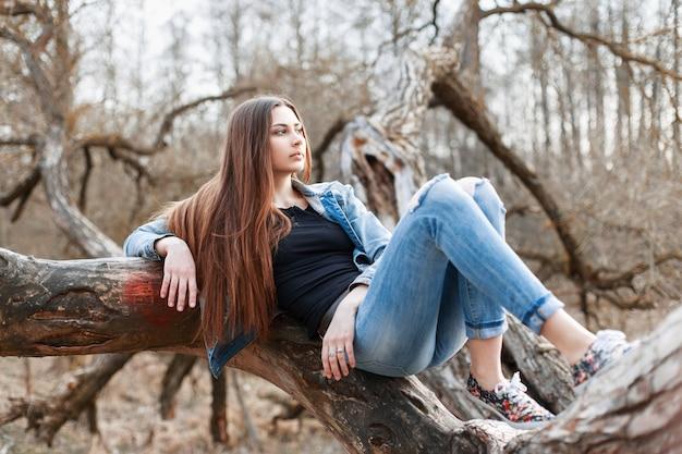 Hipster młoda dziewczyna z długimi włosami i dżinsową kurtką leżącą na drzewie