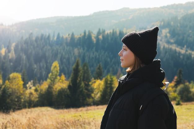 Hipster młoda dziewczyna z plecakiem, podziwiając zachód słońca na szczycie góry. turystyczny podróżnik na tle układu krajobrazowego doliny