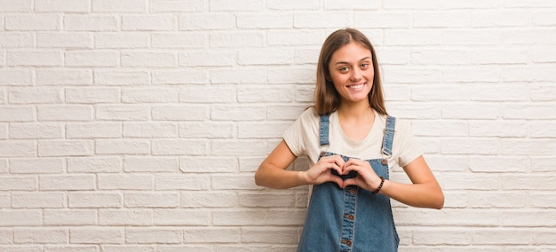 Hipster młoda kobieta robi kształt serca rękami