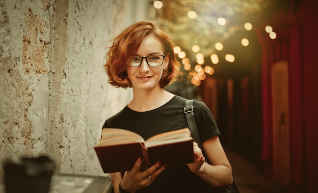 Hipster młoda kobieta w okularach z krótkimi fryzurami, czytanie książki na ulicy na świeżym powietrzu