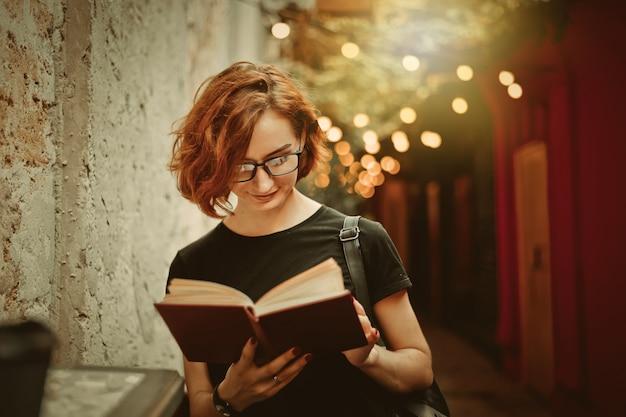 Hipster młoda kobieta w okularach z krótkimi fryzurami, czytanie książki w kawiarni na świeżym powietrzu przy ulicy