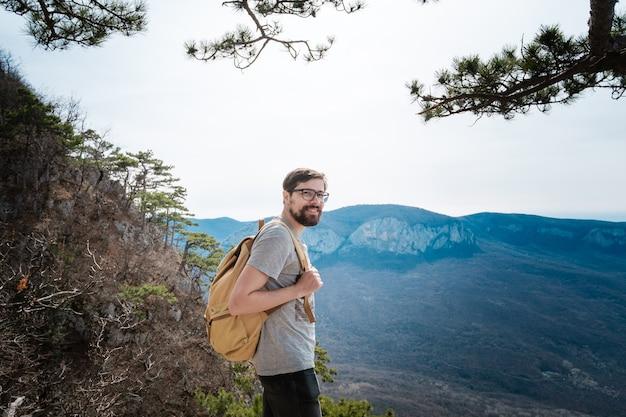 Hipster młody człowiek w górach wiosną. hipster z plecakiem za plecami wyrusza na wycieczkę