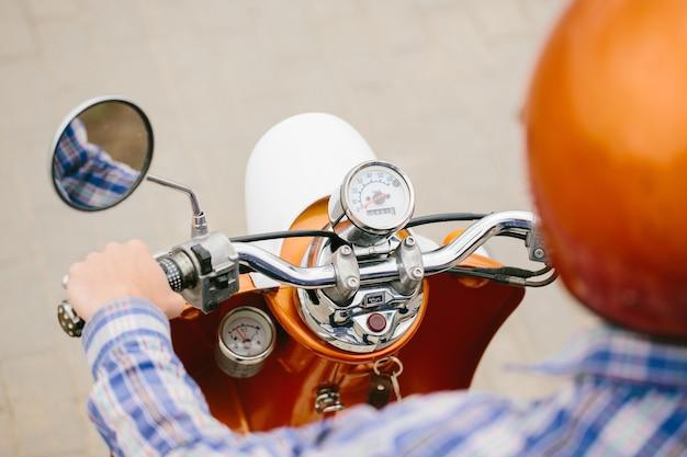 Hipster młody człowiek w kasku jedzie na żółtym skuterze retro w mieście