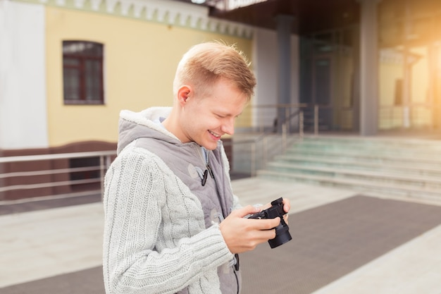 Hipster młody człowiek z aparatem w mieście, koncepcja podróży
