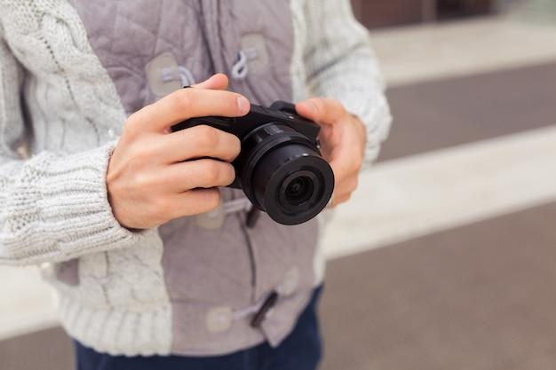 Hipster młody człowiek z aparatem w mieście, zbliżenie koncepcji podróży