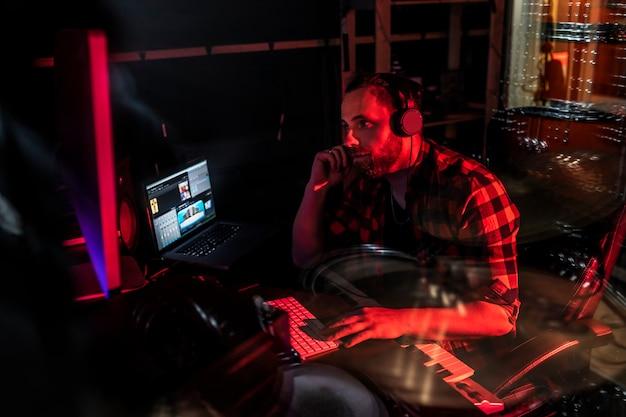 Hipster młody człowiek z brodą nagrywa nowy utwór w studiu stereofonicznym za pomocą miksera i mikrofonu.