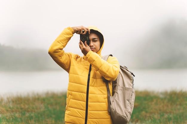 Hipster młody człowiek z jasną kurtką robi zdjęcie niesamowitego krajobrazu na mglistym tle vintage