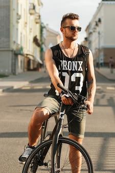 Hipster młody człowiek z rowerem siedzi na rowerze